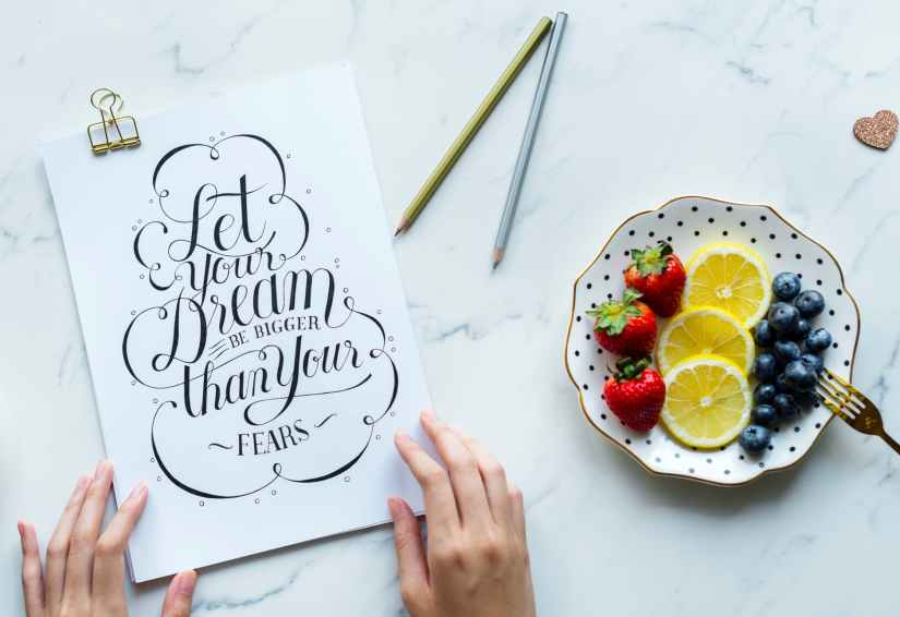 let your dream be bigger than your fears signage beside plate with fruits